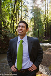 A man is wearing a bright green neck tie in the forest or woods. The man is ruggedly handsome and he is of Latino, Mexican, or Hispanic descent. The picture is of a green thinking businessman in a close to nature scenario.